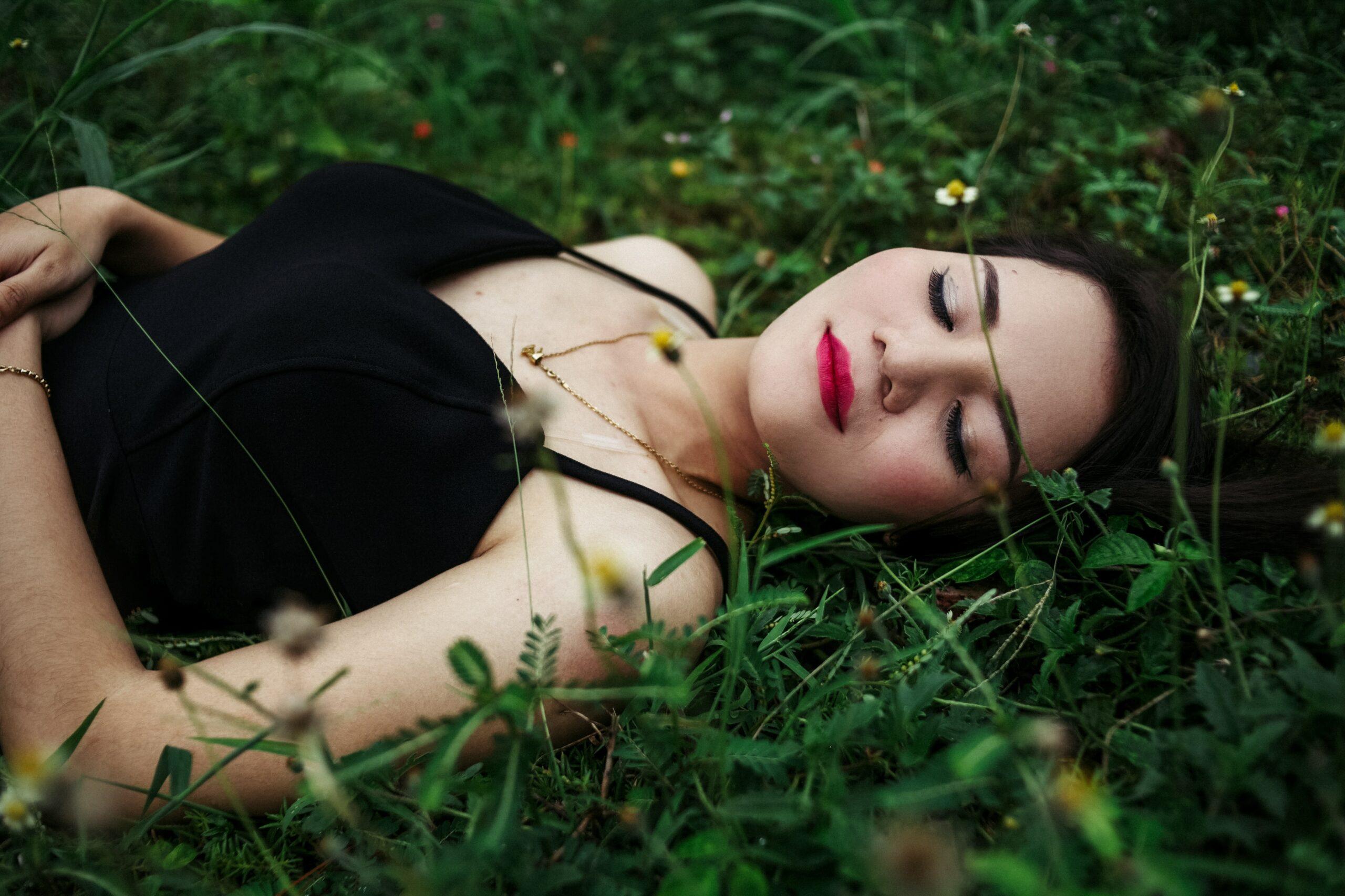 Frau schläft im Gras