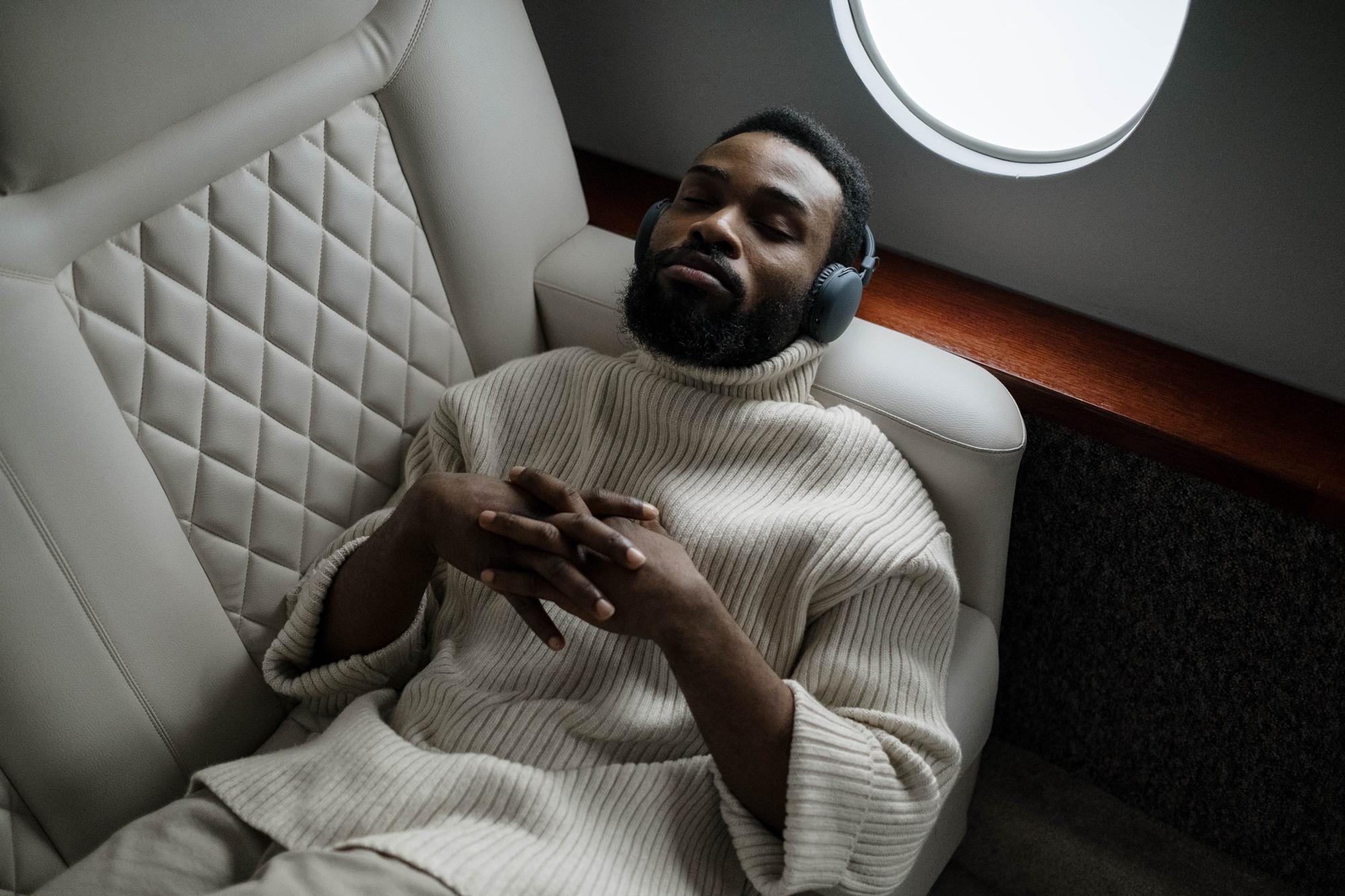 Mann schläft im Flugzeug mit Kopfhörern