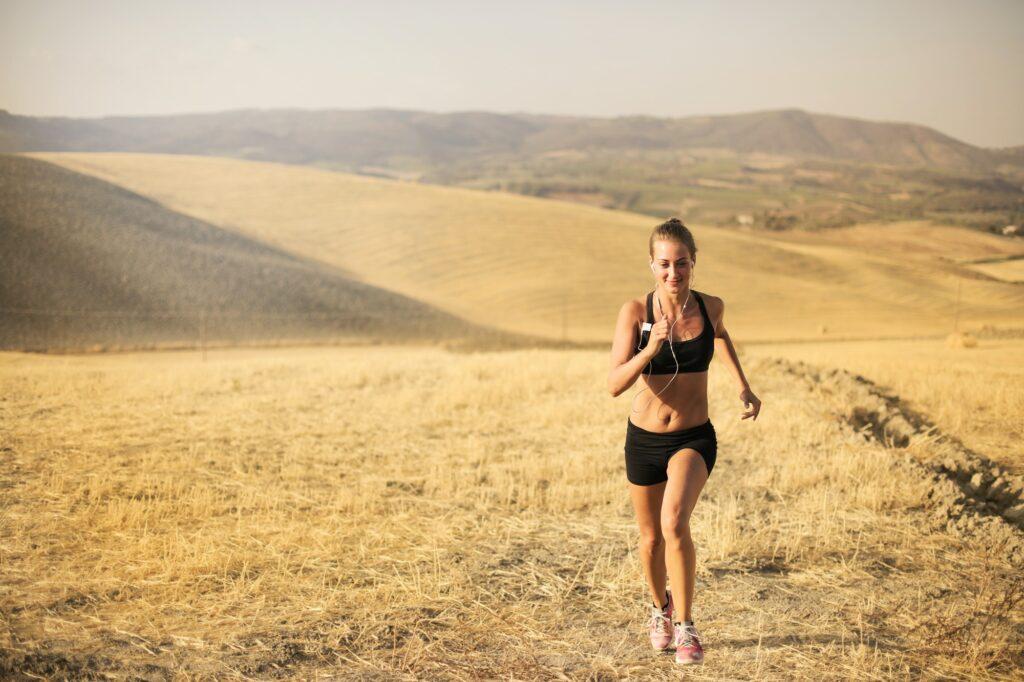 Frau rennt in warmer Graslandschaft